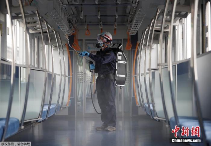 当地时间7月9日,日本东京,一名戴着防护面具和护目镜的东京地铁员工对车厢进行消毒。