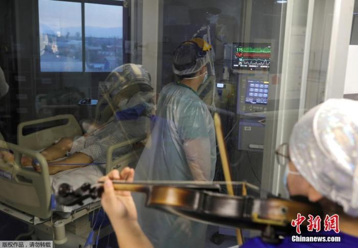 当地时间7月9日,智利圣地亚哥,埃尔皮诺医院护士为重症监护室内新冠肺炎患者演奏小提琴。