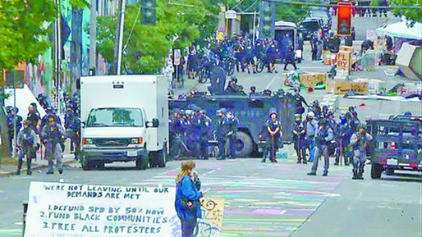 """▲7月1日,美国西雅图,全副武装的警察开着装甲车闯入""""自治区""""清场,逮捕了至少31人。据悉,6月初,西雅图抗议者占领了国会山区西雅图警察局东分局,并宣称成立""""国会山自治区""""。(环球时报)"""