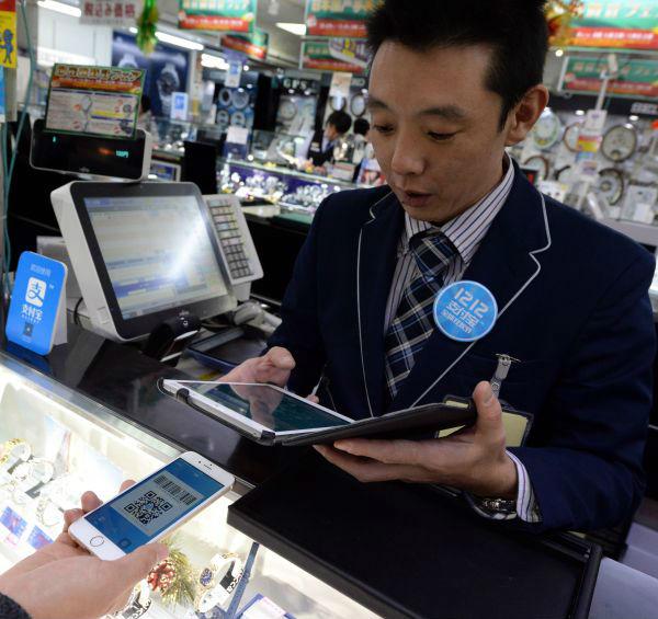 资料图:在日本都城东京,一家阛阓的伙计利用支付宝为主顾结账。新华社