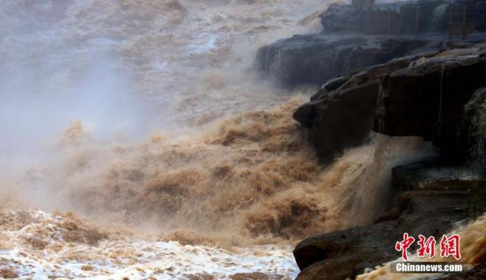 7月21日,晋陕大峡谷的黄河壶口段受黄河中上游降雨和水库调水影响,水流量大增,使得壶口主副瀑布连成一线,游客们在这里欣赏到难得一见的绵延数百米的壮美瀑布群。图片来源:人民视觉