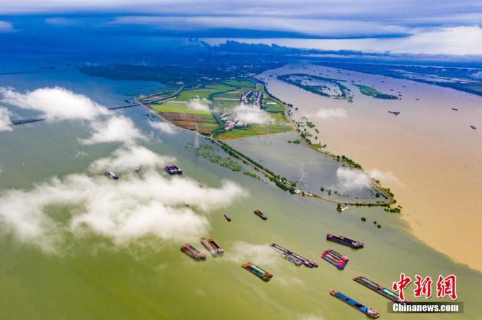 7月27日,江西省湖口县鄱阳湖和长江交汇处的水面上腾起缕缕云雾,呈现泾渭分明的两色景观。 张玉 摄