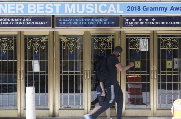 图说: 6月29日,行人从美国纽约一家停业的百老汇剧院旁走过。新华社记者 王迎 摄