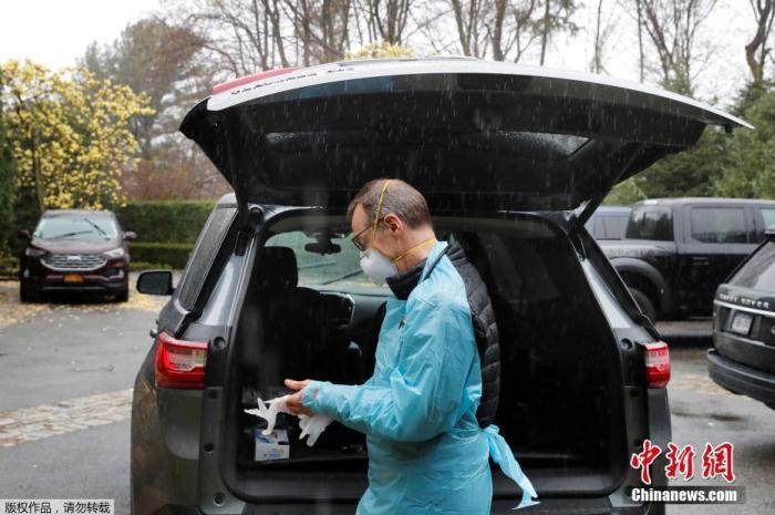 资料图:美国的格雷格·古尔布兰森医生在对一名被确诊患有新冠肺炎的患者进行家访前,穿上防护设备。