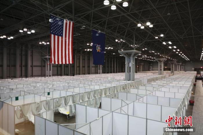 当地时间3月30日,纽约贾维茨中心临时医疗点建成,一排排病床隔间整齐排列在会展中心展场内。中新社记者 廖攀 摄