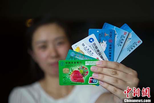 资料图:民众展示银行卡。 中新社记者 张云 摄