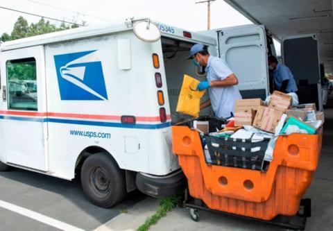 一名邮递员正在投递邮件。(图源:Getty)