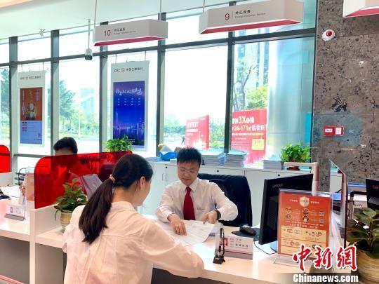 资料图:银行工作人员正在为客户服务。 赵玎 摄