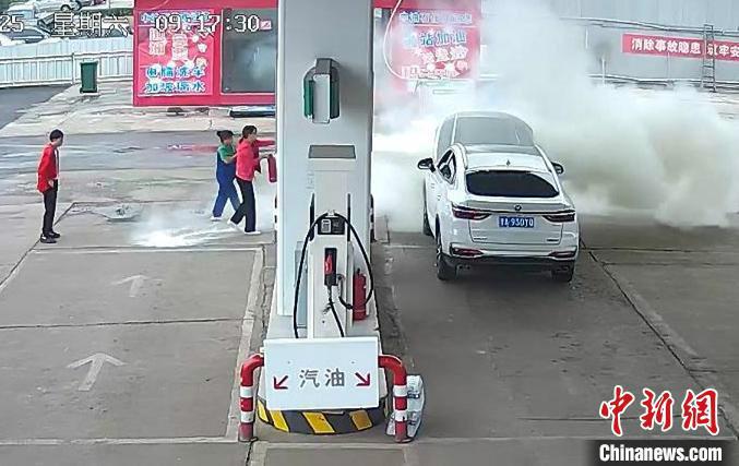 加油员和车主正在对汽车发动机部位明火进行扑救。 视频截图