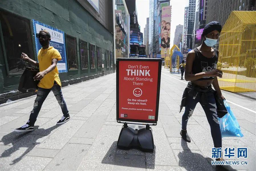 ▲7月23日,在美国纽约时报广场,人们从保持社交距离的提示牌旁走过。(新华社记者 王迎 摄)