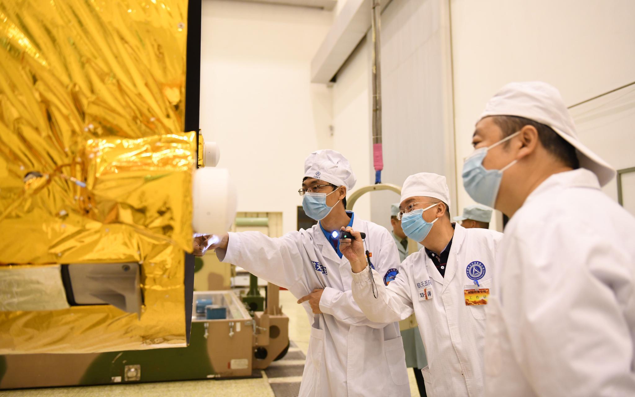 工程职员在发射场对高分多模卫星举行查抄。图/航天科技团体五院