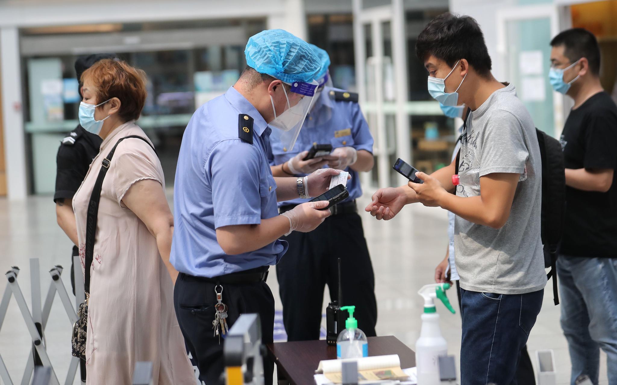 北京南站,车站事情职员通过手持终端装备核验游客的购票信息。拍照/新京报记者 王贵彬