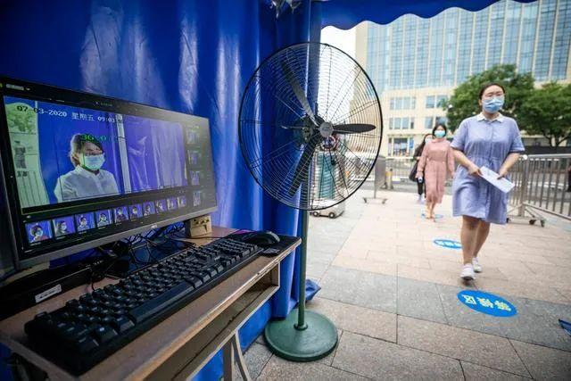 北京市第十 二。中学考点先生在模仿演练考生经由测温装备后进入考点(图源:新华社)