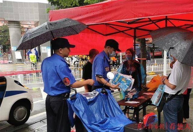 狂风暴雨中,武汉城管送雨衣给考生家长遮雨