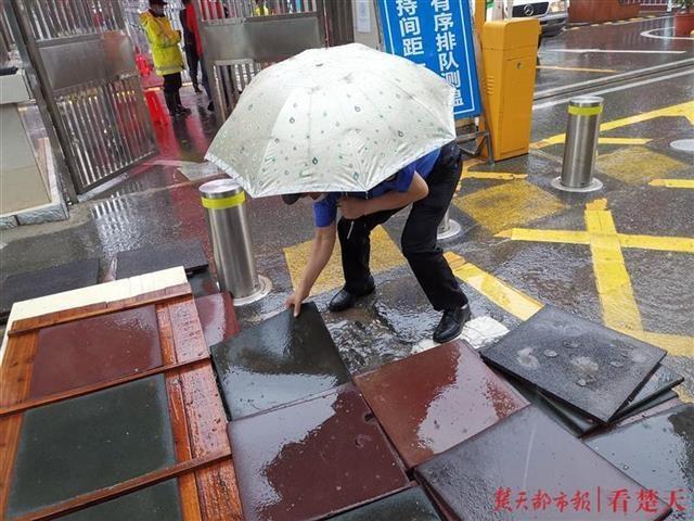 贴心护考!洪山城管队员在考点门口铺设防滑垫