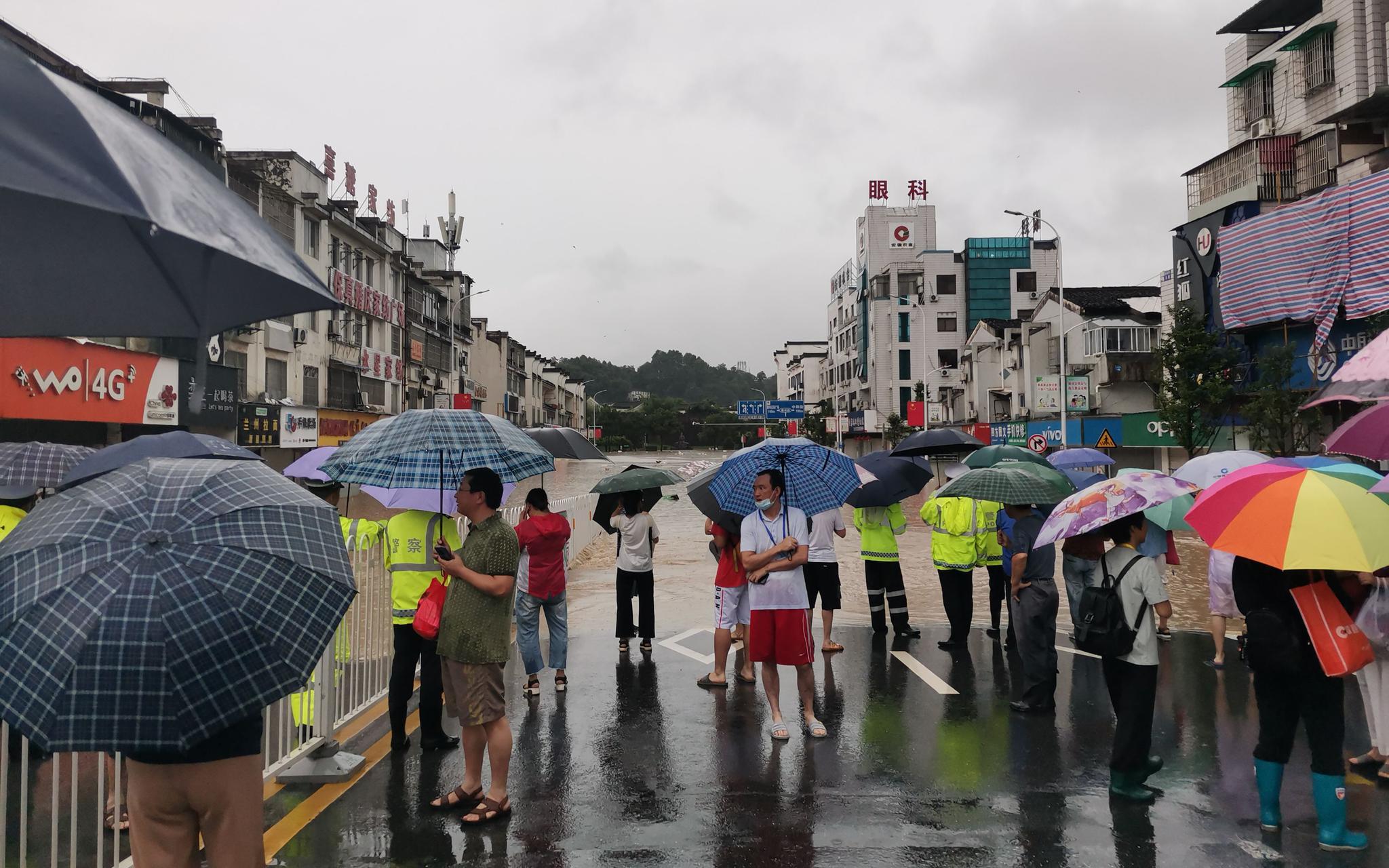 7月7日,河道洪水漫上街道,警方在现场维持秩序。受访者供图