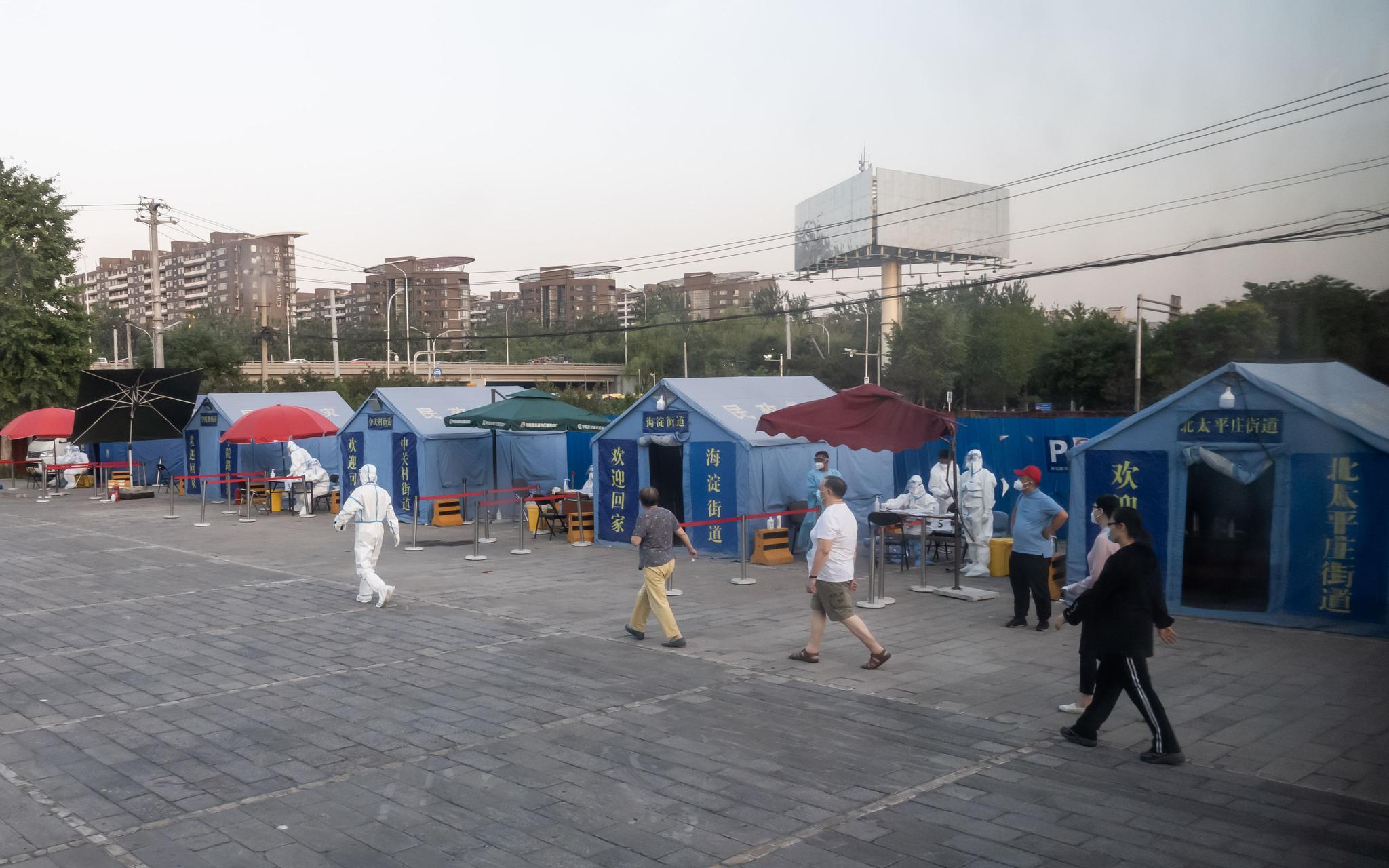 6月15日,海淀区四序青桥四周绿馨故里建材市场,市民在事情职员的指导下,预备担当咽拭子样本收罗。新京报记者 李凯祥 摄