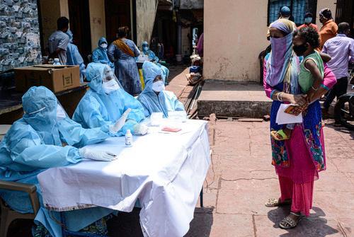 4月18日,医务人员与印度孟买塔拉维贫民窟的居民交谈。新华社发