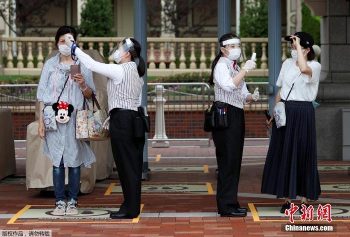 资料图:当地时间7月1日,日本东京迪士尼乐园和东京迪士尼海洋乐园恢复营业。图为游客佩戴口罩,进行体温检测。