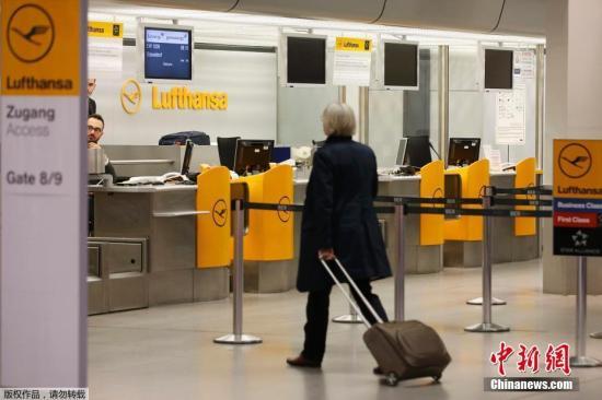资料图:德国柏林,一名旅客从汉莎航空值机柜台前走过。