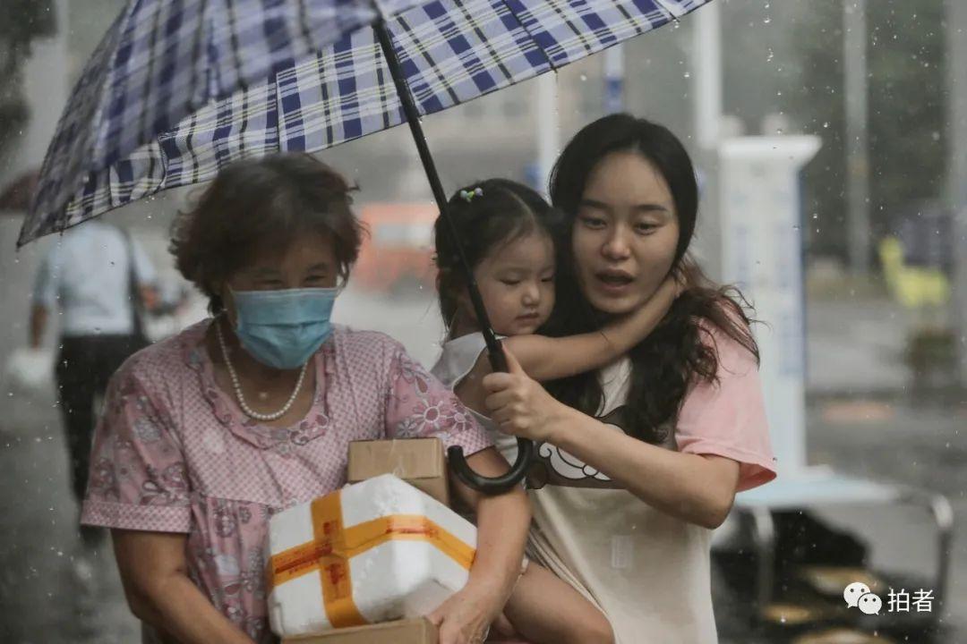 △ 复兴路,小女孩紧紧抱在打伞家长的怀中。摄影/新京报记者郑新洽