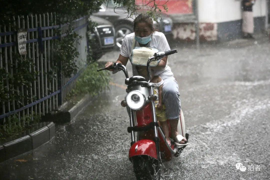 △上午,复兴路,市民冒雨骑车并为孩子遮雨。摄影/新京报记者郑新洽