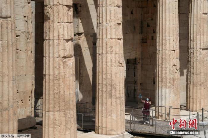 资料图:一名戴口罩的游客在参观希腊雅典卫城。