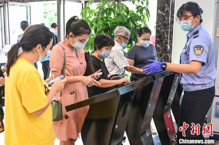 珠海居民在出入境大厅的工作人员指引下领取预约号 陈骥旻 摄