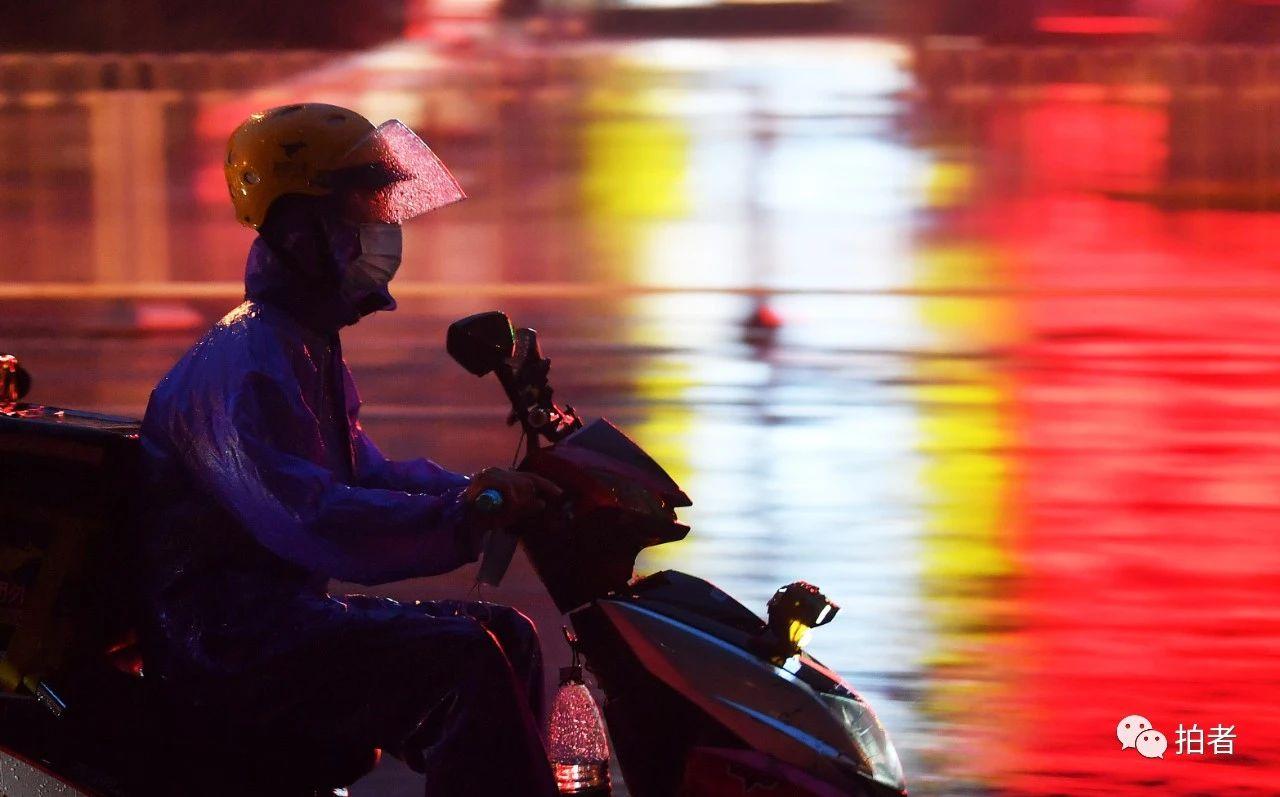 △东四十条桥西公交站附近,冒雨送外卖的小哥。摄影/新京报记者李木易