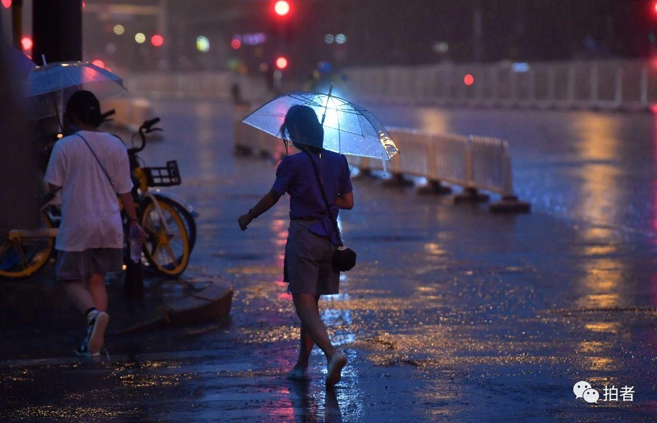 △东四十条桥西公交站附近,市民走在雨中。摄影/新京报记者李木易