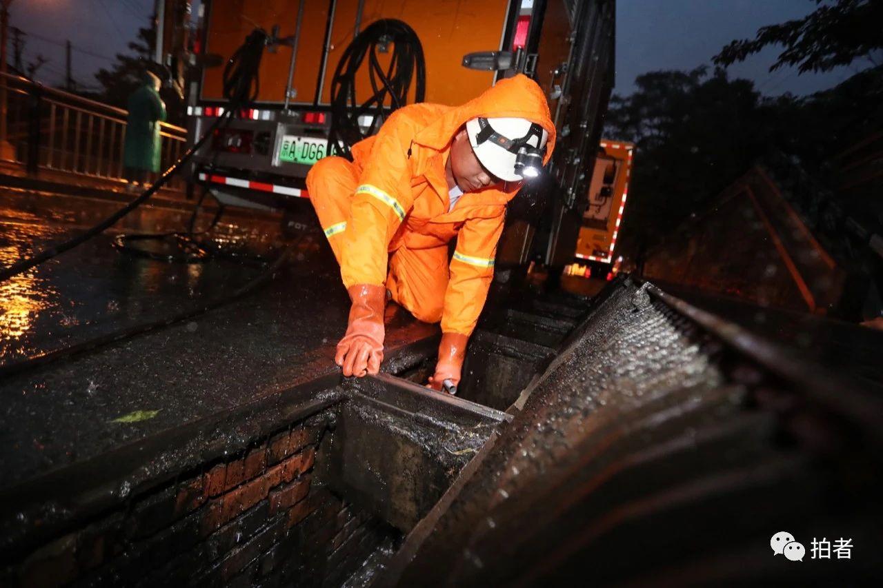 △夜间,西大望路附近,北京排水集团工作人员及时清理雨水口。摄影/新京报记者王贵彬