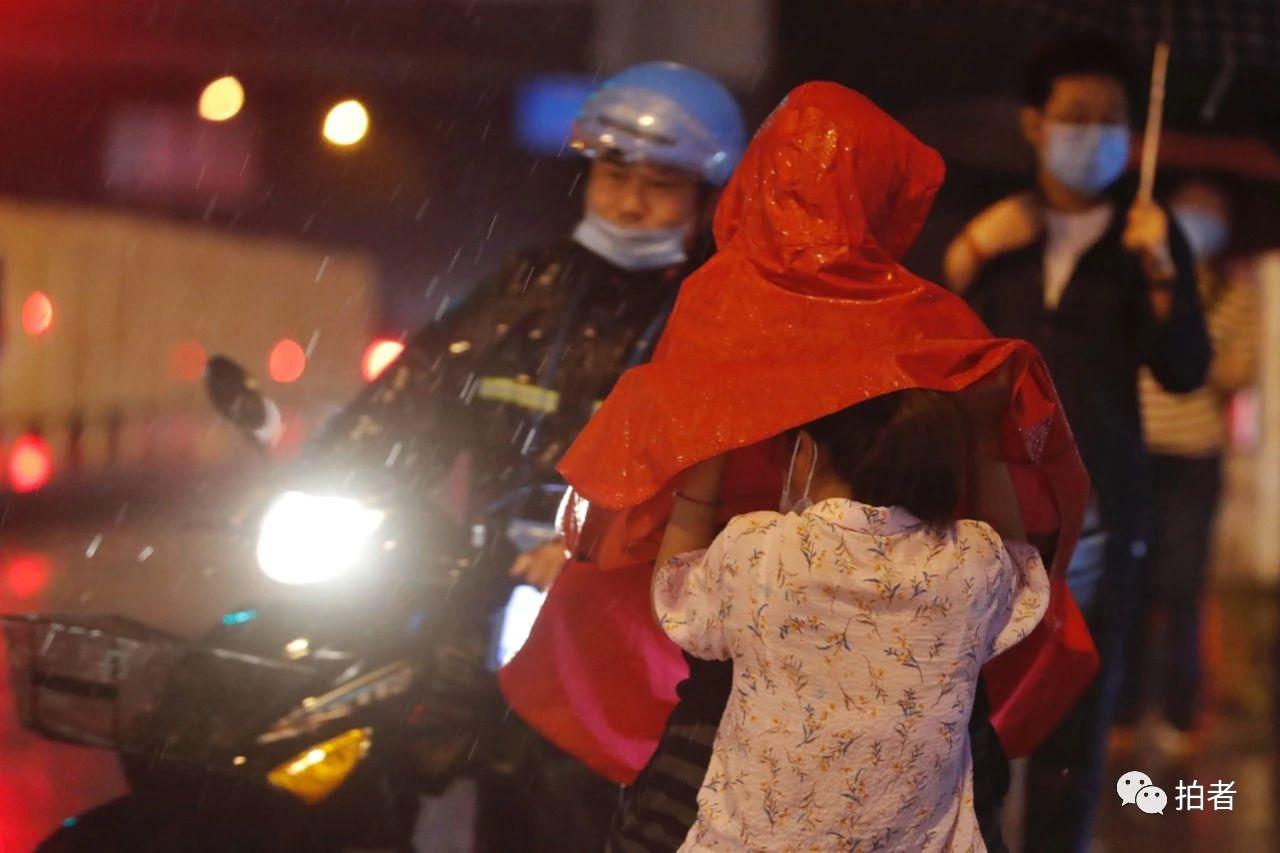 △双桥,小女孩钻进家长的雨衣里。摄影/新京报记者侯少卿