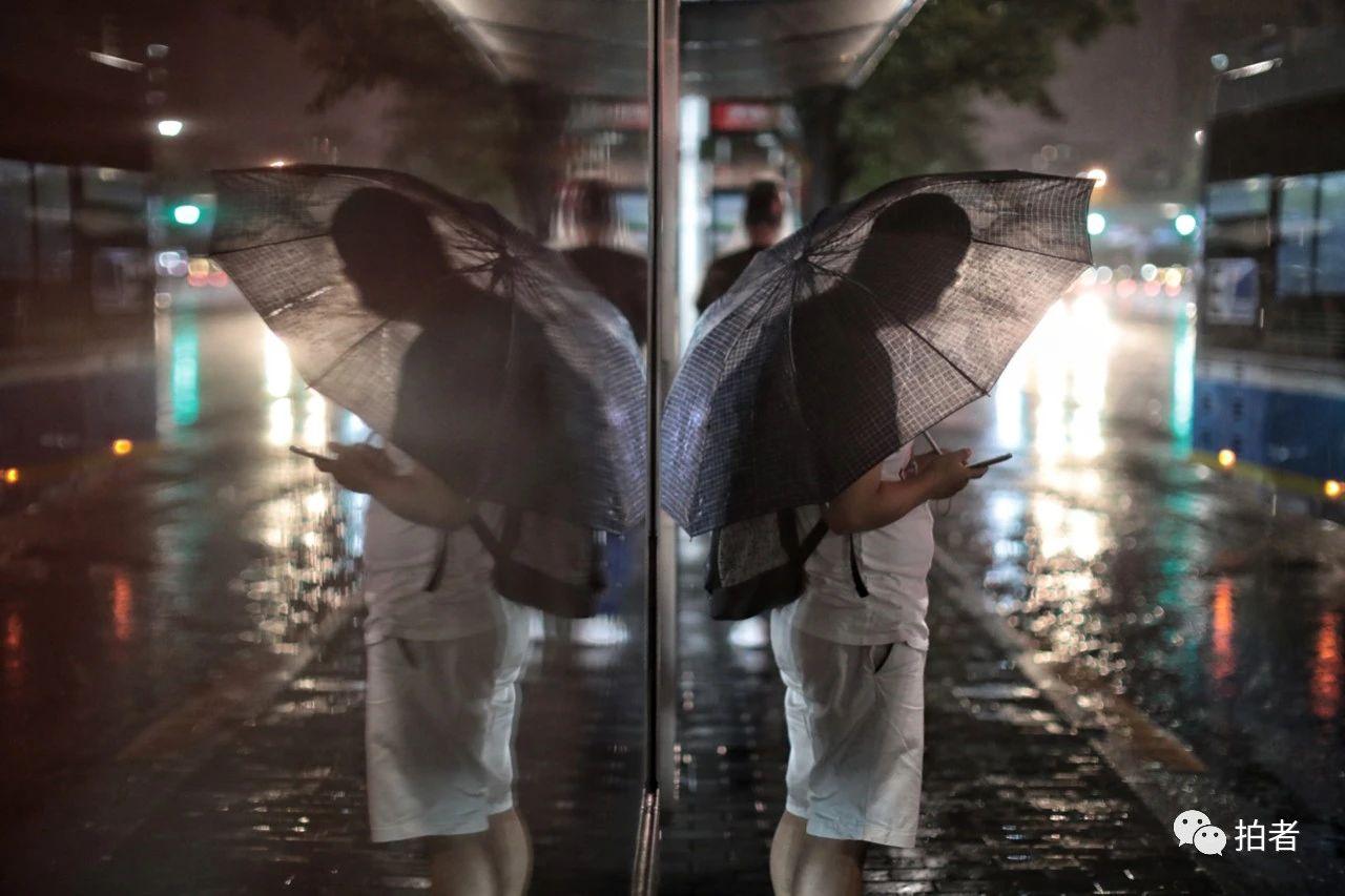 △蒲黄榆,边玩手机边等公交车的男士。摄影/新京报记者王嘉宁