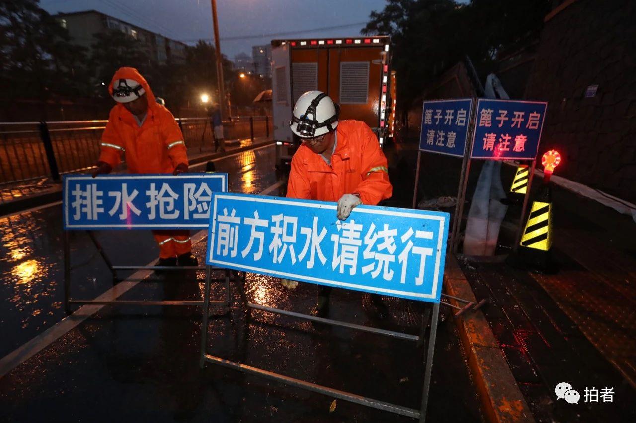 △18时30分前后,北京朝阳区雨势增大,在西大望路附近,20分钟左右路边就出现了积水。工作人员摆放排水抢险提示牌。摄影/新京报记者王贵彬