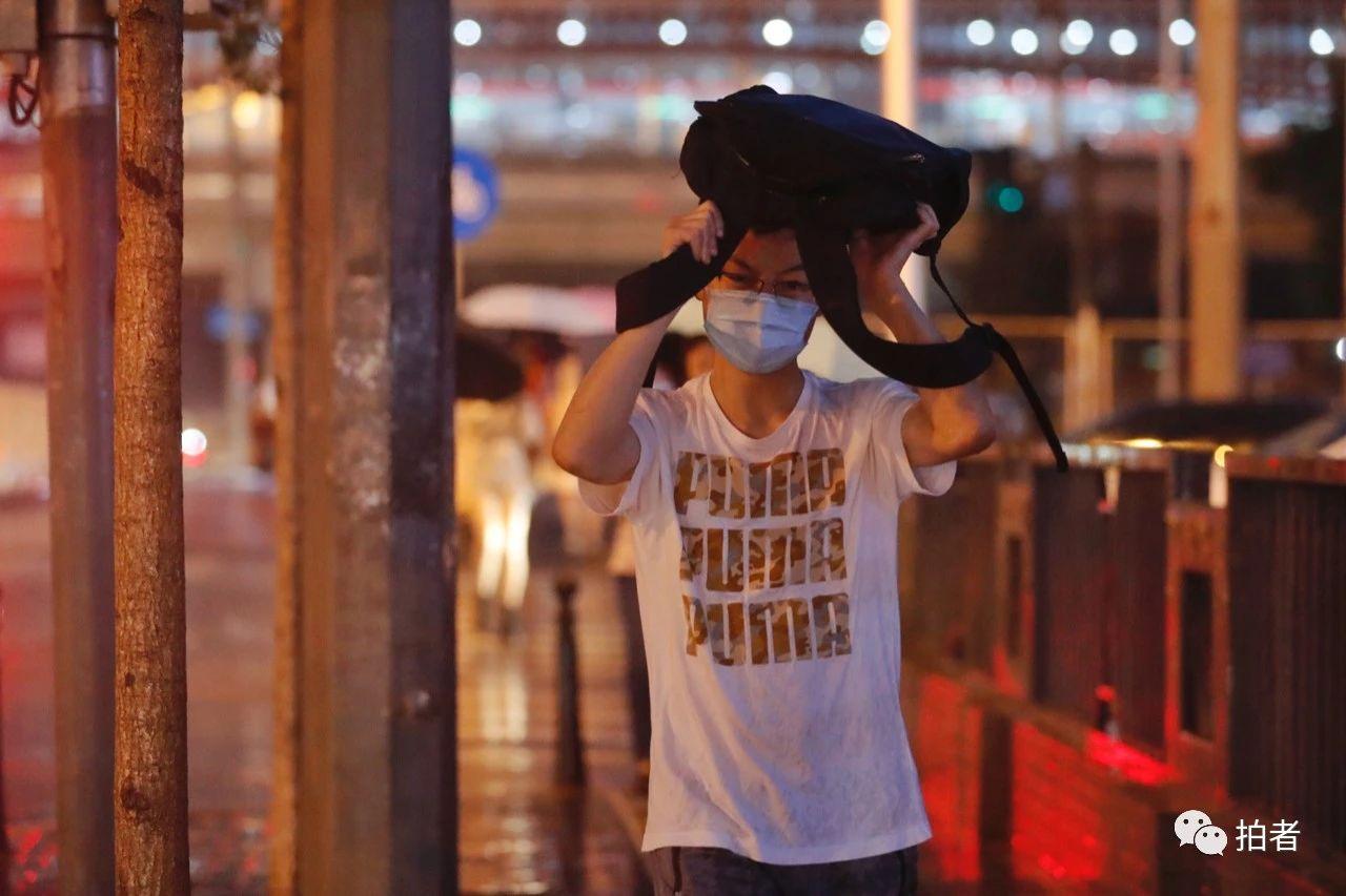 △双桥,用包挡雨的市民。摄影/新京报记者侯少卿