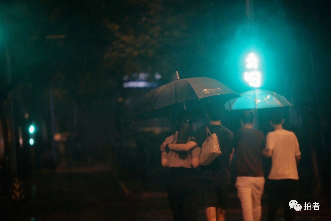 △苏州街,搂在一起撑伞过马路的行人。摄影/新京报记者郑新洽