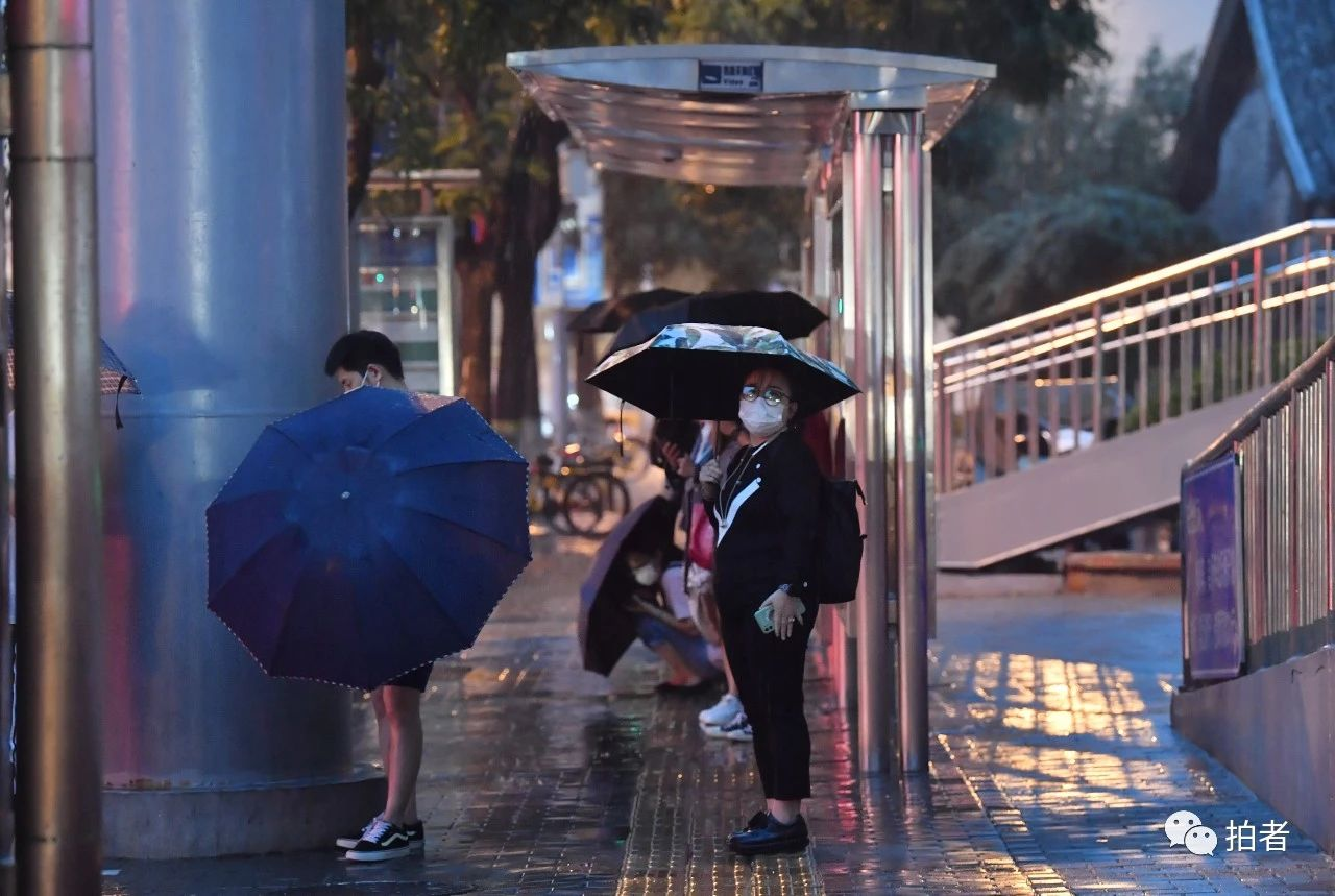 △东四十条桥西公交站附近,在过街桥下避雨的市民。摄影/新京报记者李木易