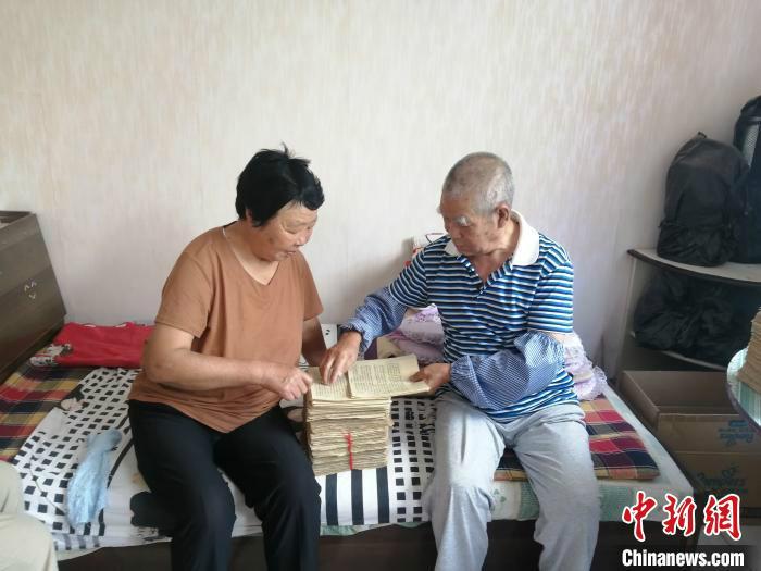原开心与家人一起整理抄写好的纸张。潞州区融媒体中心供图