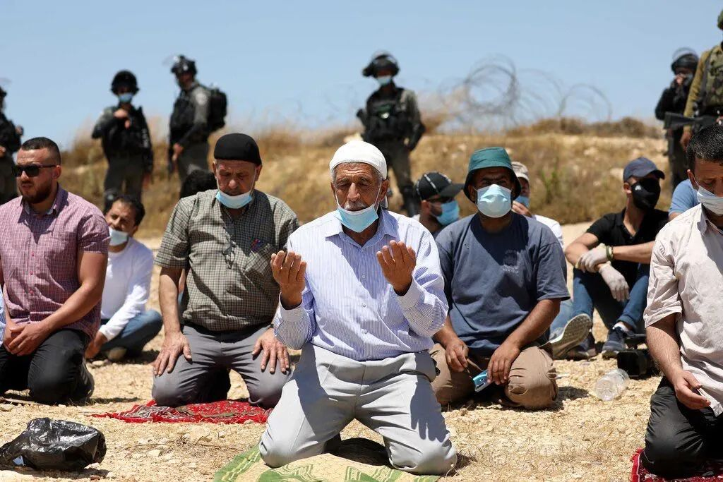 在以色列士兵的监视下,巴勒斯坦男子在计划成为西岸以色列定居点的土地上祈祷。