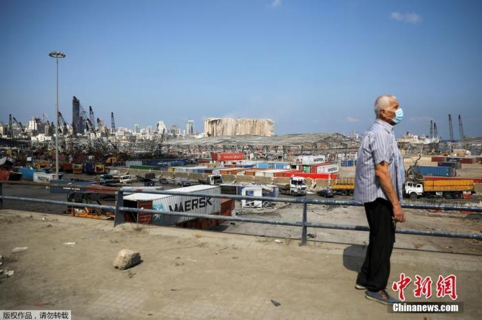 图为8月12日在黎巴嫩贝鲁特,一个戴着口罩的男子正在注视着大爆炸中被破坏的港口。