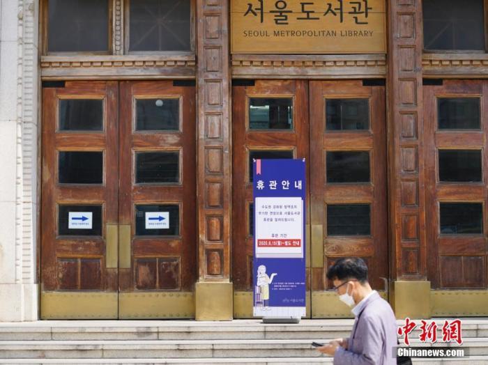 资料图:2020年6月23日,一位韩国首尔市民经过首尔市立图书馆门前,该图书馆贴出闭馆通知。近来,包括韩国首尔、仁川、京畿道在内的首都圈确诊病例持续增加。 中新社记者 曾鼐 摄