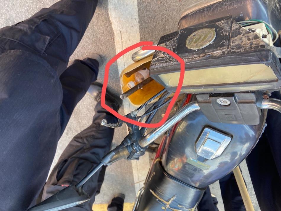 图说:8月16日16时27分,曾春亮在山砀镇航桥村十字路口被抓获,其所骑摩托车头塑料桶内,放着一把锤头和尖刀。