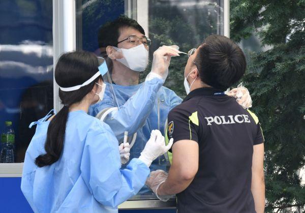19日,医务工作者在给参加集会执勤的韩国警官做病毒检测。(法新社)