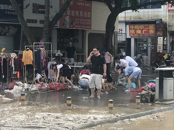 洪涝致沿街商铺受损,经营者清理淤泥以及被污水浸染的物品。本文图片 澎湃新闻记者 何利权 摄
