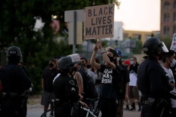 """▲资料图片:5月27日,在美国洛杉矶,一名抗议者手持写有""""黑人的命也是命""""字样的标语参加抗议活动。(新华社)"""