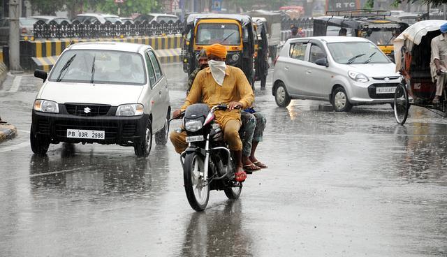 印度许多地方下大雨 人们拿着罐子挡雨