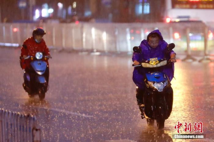 资料图:民众冒雨出行。中新社记者 盛佳鹏 摄