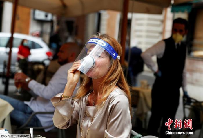 图为戴面罩的女士在意大利罗马街头喝咖啡。