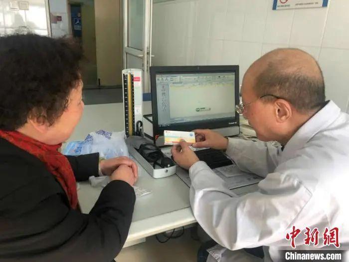 资料图:一位医生在给患者介绍药品。 王怡苹 摄