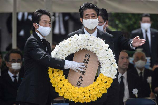 8月9日,在日本长崎和平公园,日本首相安倍晋三(右)参加活动。新华社/法新